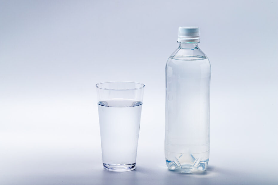 Photo of a glass of water and a small bottle of water. The glass is on the left and the bottle on the right. The background is white. The bottle is plain and without a sticker or branding. The photo gives an idea of cleanliness, simplicity, lightness, almost clinical.
